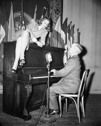 Then-Vice President Harry Truman plays the piano, with Bacall perched on top, during her appearance at the National Press Club in 1945.