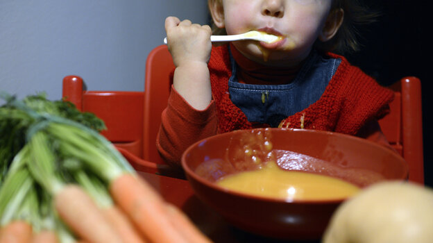 A child eats vegetable soup in Lyon, France. Many French parents expect their kids to eat sophisticated adult dishes at a young age.