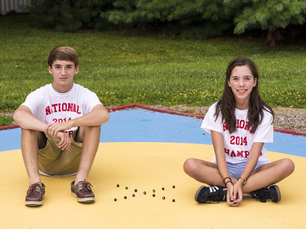 Dominic Rudakevych and Marilyn Fisher, 2014 champions of the National Marbles Championships in Wildwood, N.J., pose at the marbles rings in Middletown, Md. The two 13-year-olds train with the Frederick Coun