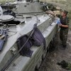 A Ukrainian soldier cleans his armored personnel carrier near Donetsk in eastern Ukraine on Monday. Russia says a large convoy that's heading to the area from Moscow is carrying humanitarian aid.