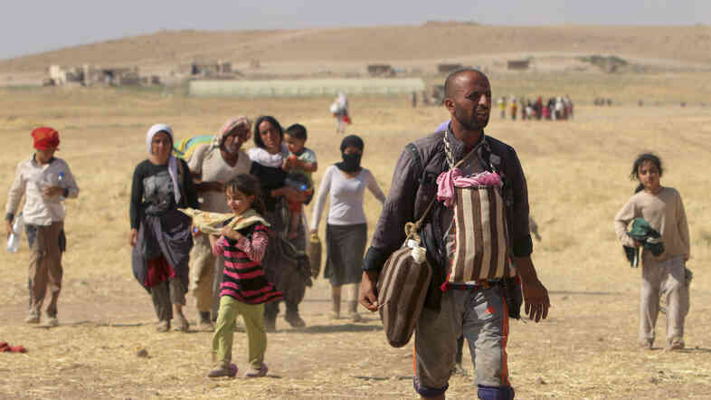 Displaced people from the minority Yazidi sect walk toward the Syrian border on the outskirts of Sinjar mountain on Monday. A U.S. assessment team says far fewer refugees are stranded on Mount Sinjar than previously thought.