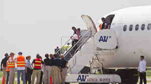 Immigration and Customs officials stand by as a woman and child, who were deported from the United States, deplane at the San Pedro Sula airport in Honduras on July 18.