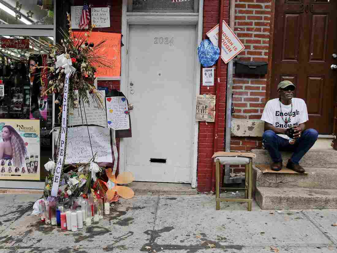 Doug Brinson sits on a stoop next to a makeshift memorial for Eric Garner in Staten Island, N.Y. Garner died after he was put in a chokehold by police officers while being arrested at the site last month for selling untaxed loose cigarettes. His death has been ruled a homicide.