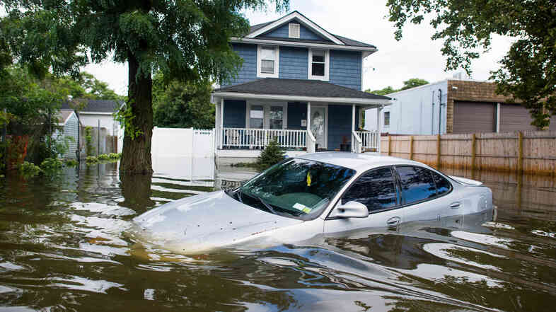 A car is abandoned on a flooded street following heavy rains and flash flooding in Bay Shore, N.Y., on Wednesday. The South Shore of Long Island along with the tri-state region saw record-setting rain that caused roads to flood.