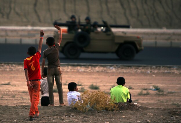 Iraqi children from the Yazidi community wave to Kurdish peshmerga forces near Dohuk, the Kurdish region of autonomous Kurdistan in Iraq. The children fled with their families from their hometown, which was attacked by Sunni militants from the Islamic State.