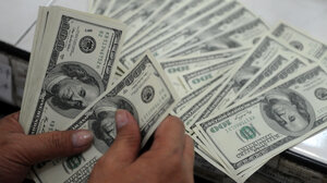 An employee at a money changer in Manila counts $100 bills in 2012. Today, more than a half-trillion dollars' worth of $100 bills are overseas.