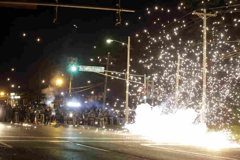 A device deployed by police goes off in the street as police and protesters clash Wednesday in Ferguson, Mo.