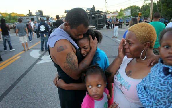 """I'm out here to stand for my children and their future,"" said Terrell Williams El, who hugged his daughter while standing with his wife and two daughters near the QuickTrip in Ferguson, Mo., Wednesday. Several other residents say they've often felt harassed by police."