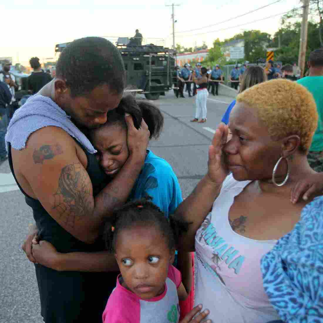 """""""I'm out here to stand for my children and their future,"""" said Terrell Williams El, who hugged his daughter while standing with his wife and two daughters near the QuickTrip in Ferguson, Mo., Wednesday. Several other residents say they've often felt harassed by police."""