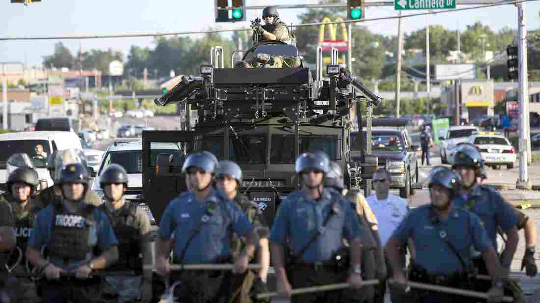 Riot police stand guard as demonstrators protest the shooting death of teenager Michael Brown in Ferguson, Mo., Wednesday. The police have been an increasingly militarized presence as the protests continued this week.