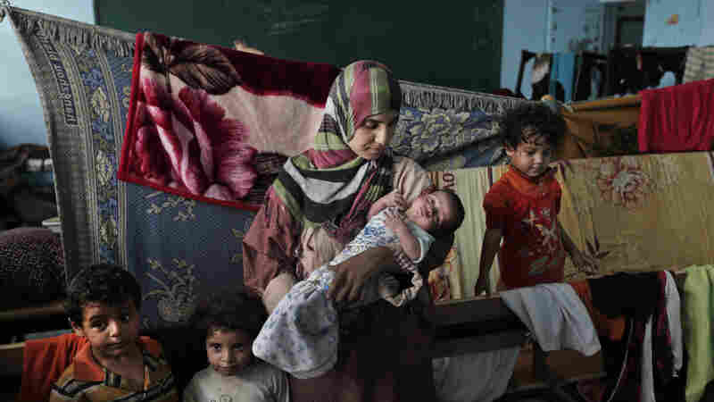 Displaced Palestinian Emada Al Attar, 23, holds her 16 day-old baby boy Anous in a classroom where they sleep in a U.N. school where the family is taking refuge during the war, in Gaza City, Gaza Strip on Aug. 8.