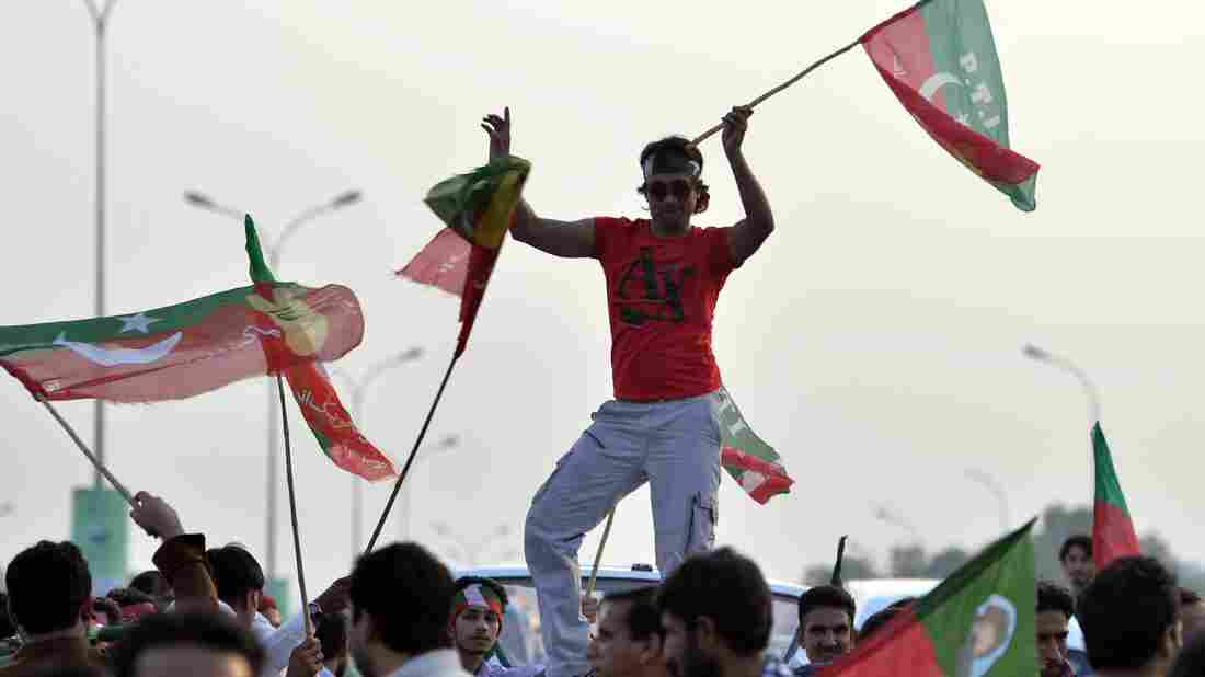 Pakistani supporters of opposition politician Imran Khan wave party flags in Islamabad on Thursday, the country's Independence Day. In addition, thousands of protesters gathered in the city of Lahore to march on the capital. They say the country's election last year was marked by fraud.