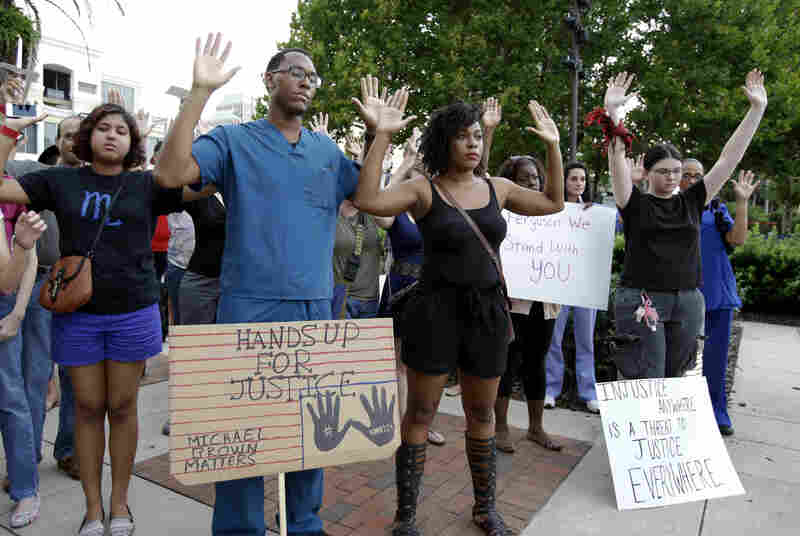 A group of people hold up their hands during a nationwide moment of silence at a vigil in Orlando, Fla. Protestors in Ferguson, Mo., say that Michael Brown, the teen whose shooting death on Saturday is at the root of tensions there, was in a similar pose when killed by a police officer.