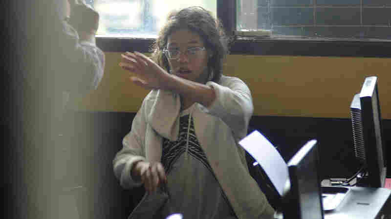 Heather Mack, the daughter of an American woman found dead inside a suitcase on the Indonesian island of Bali, gestures while in custody in a police station in Denpasar on Thursday.