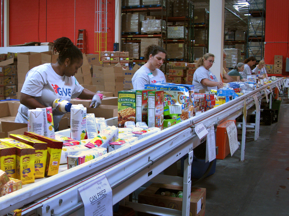 Volunteers at the Maryland Food Bank in Baltimore sort and box food donations on a conveyor belt. The bank started working with groups like the USO in 2013 to provide food aid to families affiliated with nearby military bases. (Pam Fessler/NPR)
