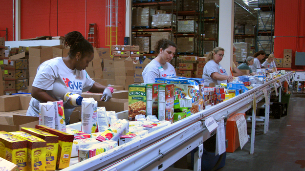 Volunteers at the Maryland Food Bank in Baltimore sort and box food donations on a conveyor belt. The bank started working with groups like the USO in 2013 to provide food aid to families affiliated with nearby military bases. (NPR)