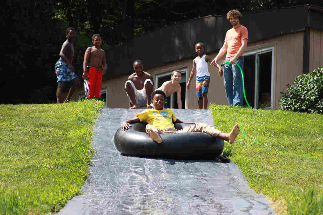 During the day, the kids visit their dads in prison. But in the late afternoon and evenings, they do activities like tubing down a giant slip-and-slide. Kobe Goodall takes his turn while his fellow campers look on.