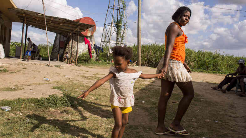 A mother and child pass through Batey Bembe in the sugar-producing region near the town of Conseulo. Bateys are small, isolated communities made up of sugar cane workers and their families, often consisting of three or four generations.