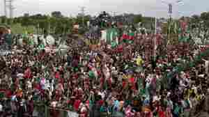 Supporters of Imran Khan, a cricketer-turned-politician and head of opposition party Pakistan Tehrik-e-Insaf, listen to his speech during a protest in Islamabad, Pakistan, on Saturday.