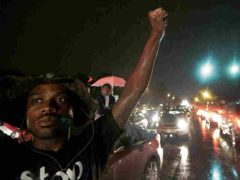 A protester holds up a clenched fist Friday night in front of a convenience store that was looted and burned in Ferguson, Mo.