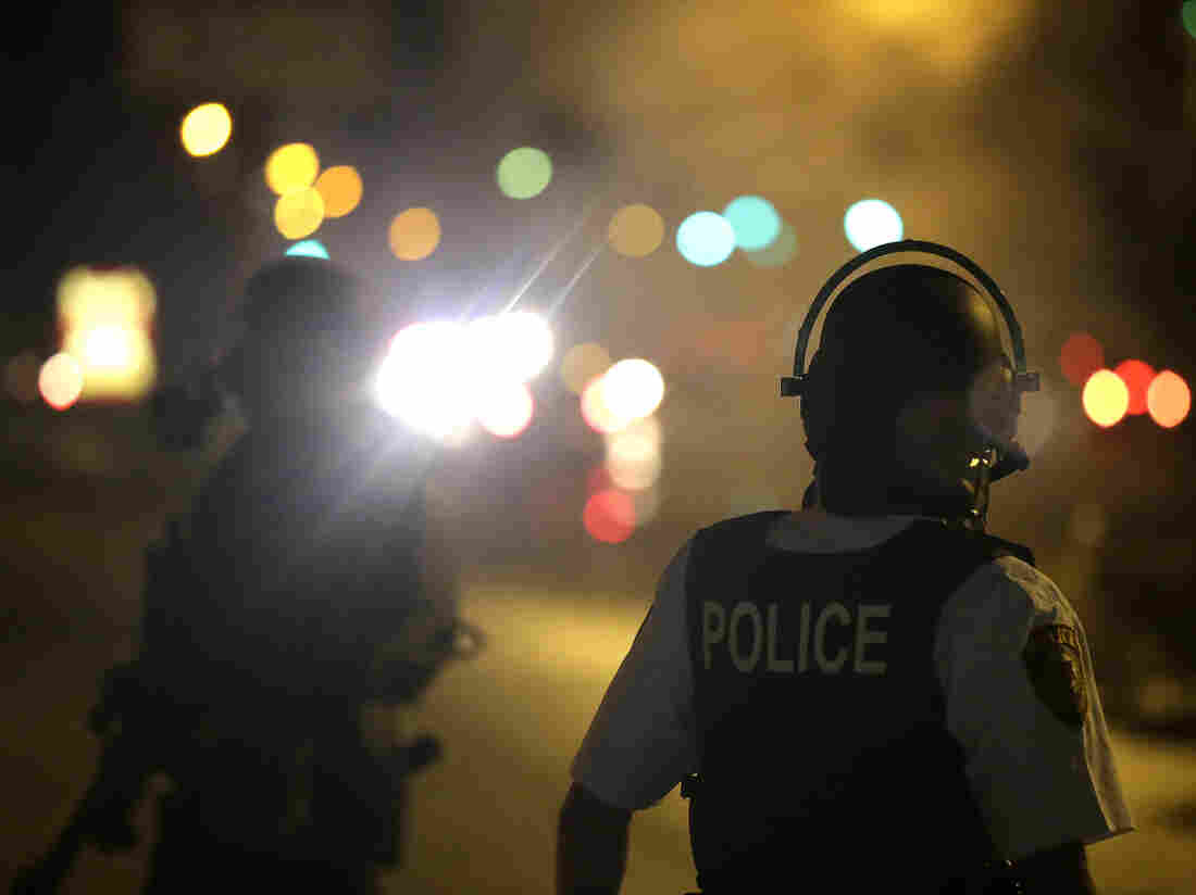 A police officer watches early Sunday as tear gas is fired to disperse protesters in Ferguson, Mo.