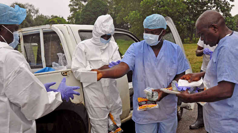 Health workers are handed personal protective gear before collecting the bodies of the deceased from streets in Monrovia, Liberia, on Saturday. Liberia is one of three West African countries hard-hit by the Ebola outbreak.
