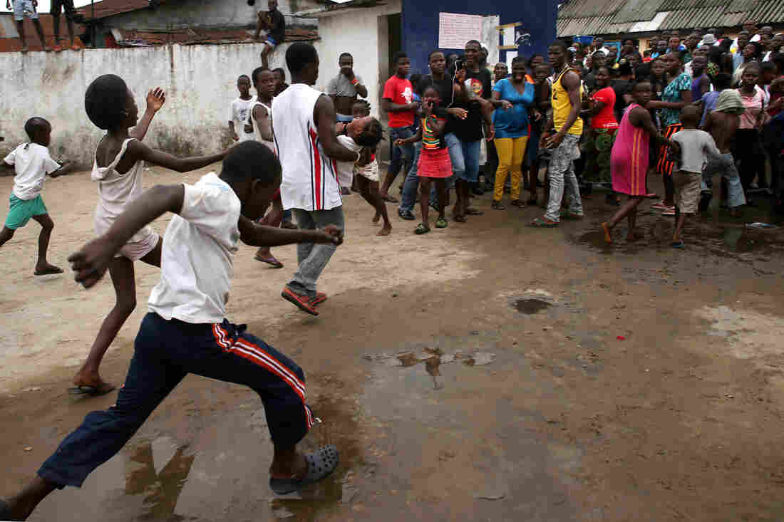 A man carries out a girl from an Ebola holding center as a mob overruns the facility in the West Point slum of Monrovia, Liberia, on Saturday.