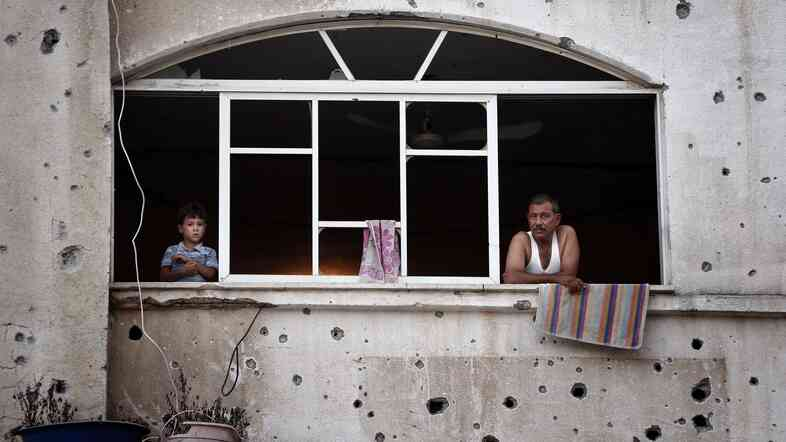 Palestinians look out of a window frame in the northern Gaza Strip city of Beit Hanun on Monday. Media reports say a cease-fire has been extended for 24 hours.