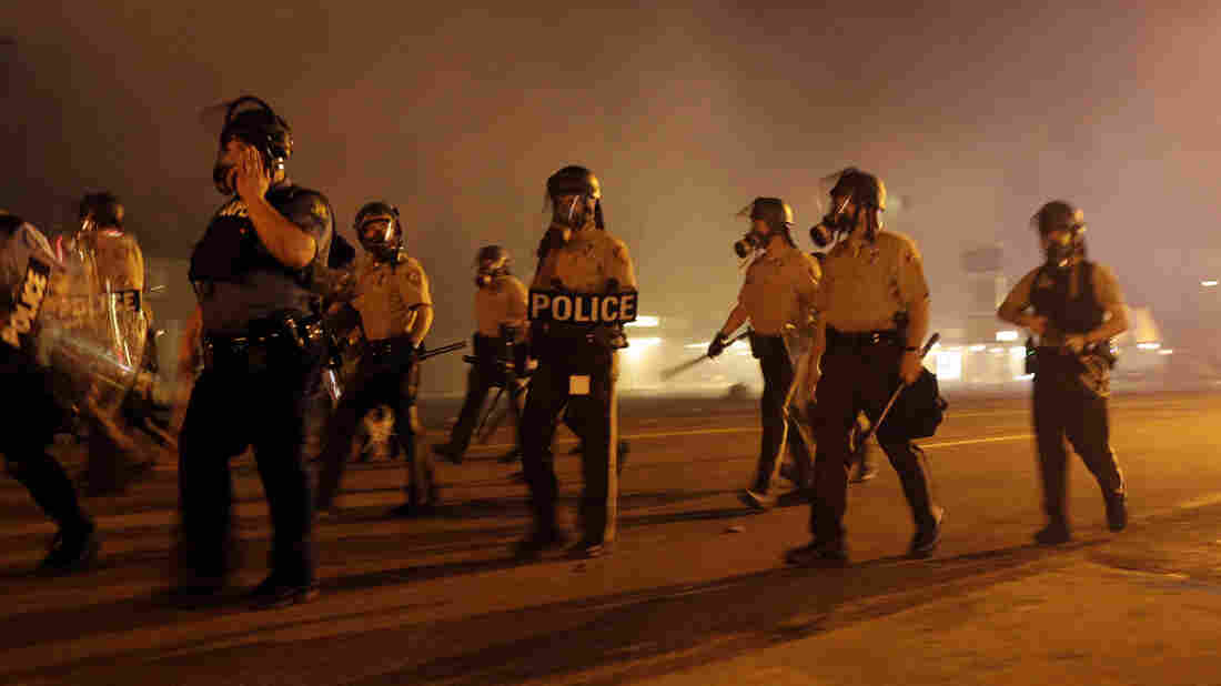 As night fell Sunday in Ferguson, another peaceful protest quickly deteriorated after marchers pushed toward one end of a street. Police attempted to push them back by firing tear gas.