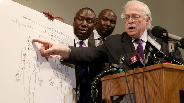 Dr. Michael Baden points to an autopsy diagram showing where bullets hit Michael Brown, as the family's attorneys Benjamin Crump (left) and Daryl Parks look on during a news conference Monday at the Greater St. Mark Family Church in Ferguson, Mo.