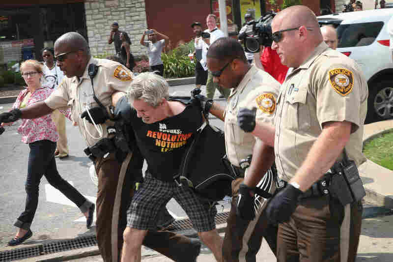 """Police arrest a demonstrator protesting the fatal police shooting of Michael Brown in Ferguson on Monday. At a news conference, President Obama called for calm. """"Let's seek to heal rather than wound each other,"""" he said."""