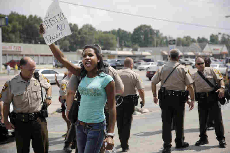 A protester holds up a sign as police try to keep protesters and media moving.