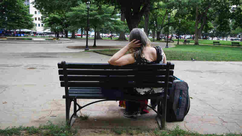 Susan sits on a park bench in Washington, D.C. She has struggled with homelessness for nearly two decades.