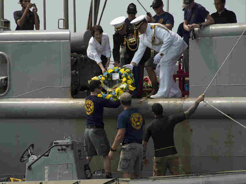 Deputy Chief of Mission (Jakarta, Indonesia) Kristen Bauer (top left), Capt. Richard Stacpoole (top right), and Marine Lt. Col. Miguel Avila pass a wreath to sailors assigned to Mobile Diving Salvage Unit One, during a wreath-laying ceremony for the sunken Navy vessel USS Houston.