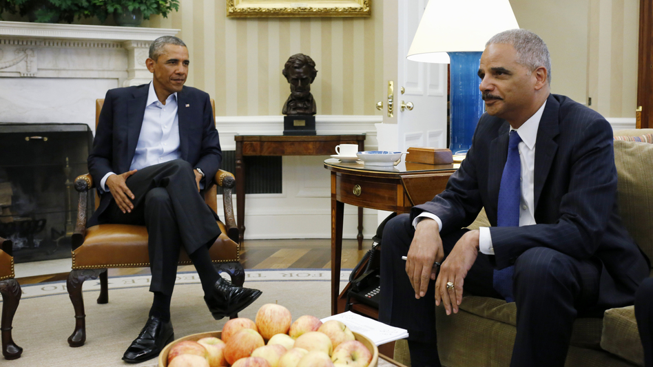 President Obama meets with Attorney General Eric Holder in the Oval Office of the White House on Monday. Holder is traveling to Ferguson, Mo., where a federal investigation is under way in the police shooting of Michael Brown, a black teenager who was unarmed.