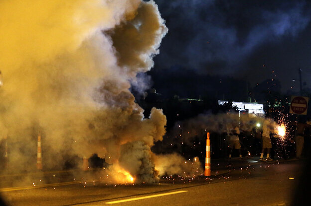 Tear gas is deployed after police were fired upon Monday in Ferguson, Mo.