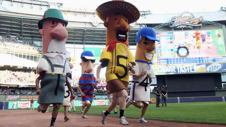 Between innings, racing sausages entertain Milwaukee Brewers fans.