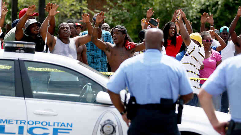 """People raise their arms while chanting, """"Hands up. Don't shoot,"""" near where St. Louis police say officers shot and killed a 23-year-old man who was wielding a knife and refused to drop it on Tuesday."""