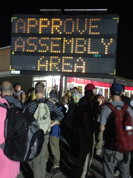 Law enforcement officials move crowds gathering in Ferguson, Mo. toward the perimeter of the designated marching area after clashes erupted on August 19, 2014.