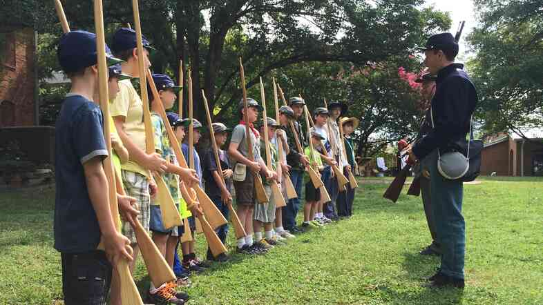 A small group of 8- to 12-year-olds learn about how soldiers trained for the Civil War.
