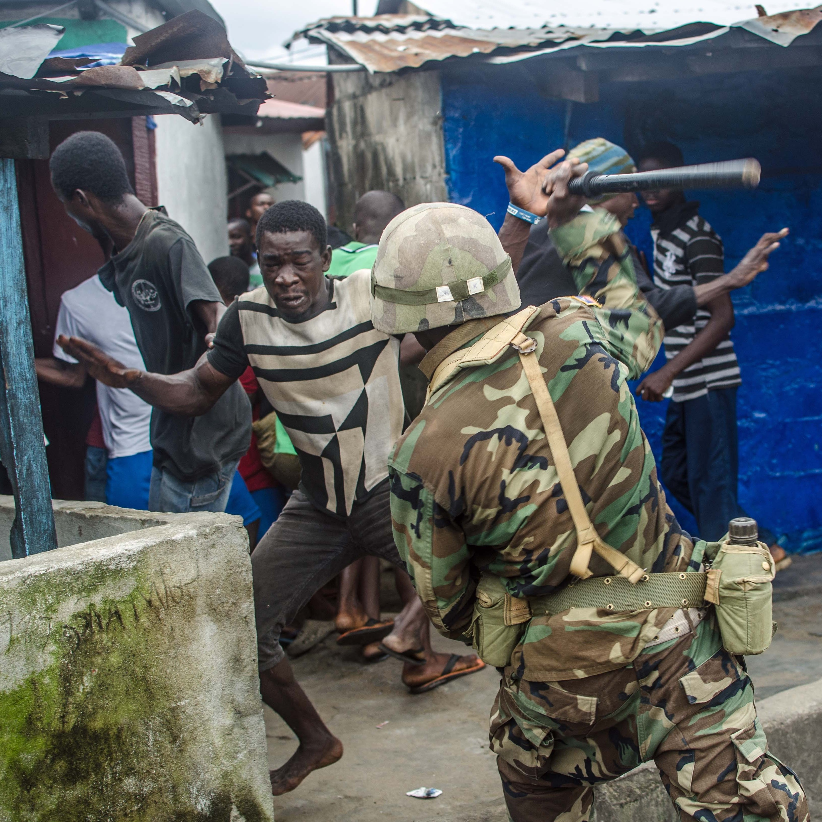 A soldier hits a protester with a baton.