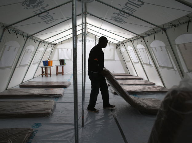 Workers with the aid group Doctors Without Borders prepare a new Ebola treatment center near Monrovia, Liberia, on Sunday. The facility has 120 beds, making it the largest Ebola isolation clinic in history.