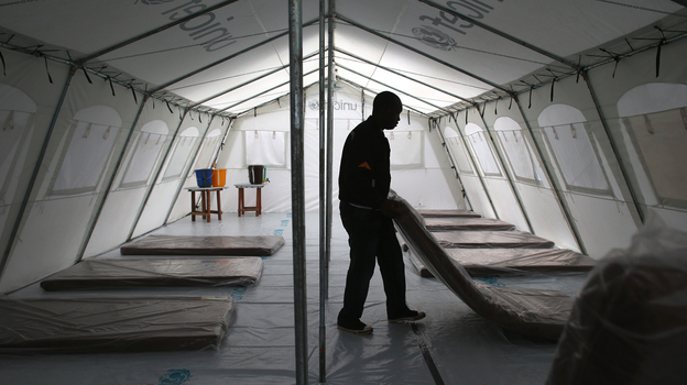 Workers with the aid group Doctors Without Borders prepare a new Ebola treatment center near Monrovia, Liberia, on Sunday. The facility has 120 beds, making it the largest Ebola isolation clinic in history. (Getty Images)