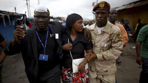 Government officials escort the commissioner of West Point, Haja Miatta Flowers, out of the neighborhood.