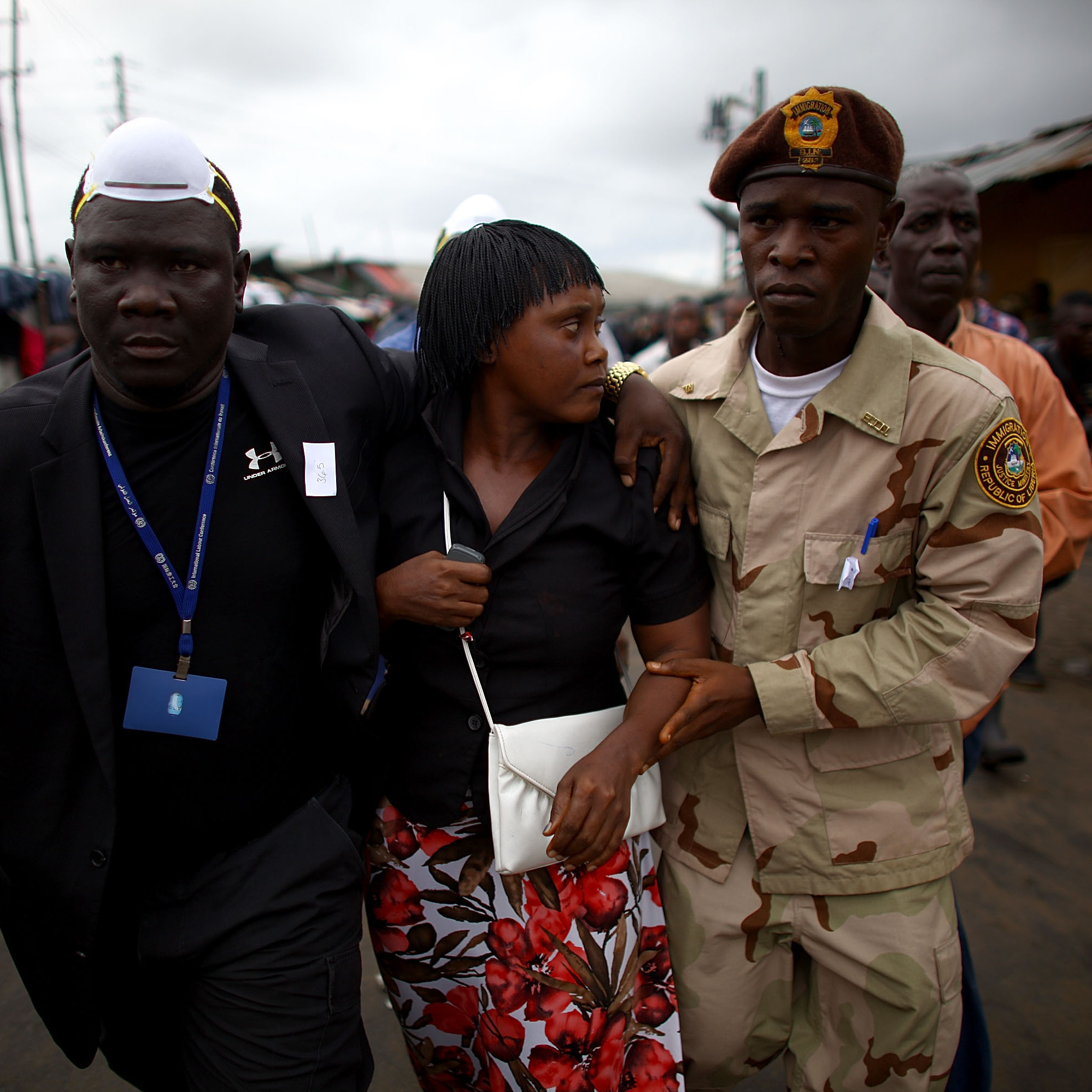 Government officials escort the commissioner of West Point, Haja Miatta Flowers, out of the neighborhood. She had returned to bring out her children, sparking Wednesday morning's riot in the Monrovia slum.