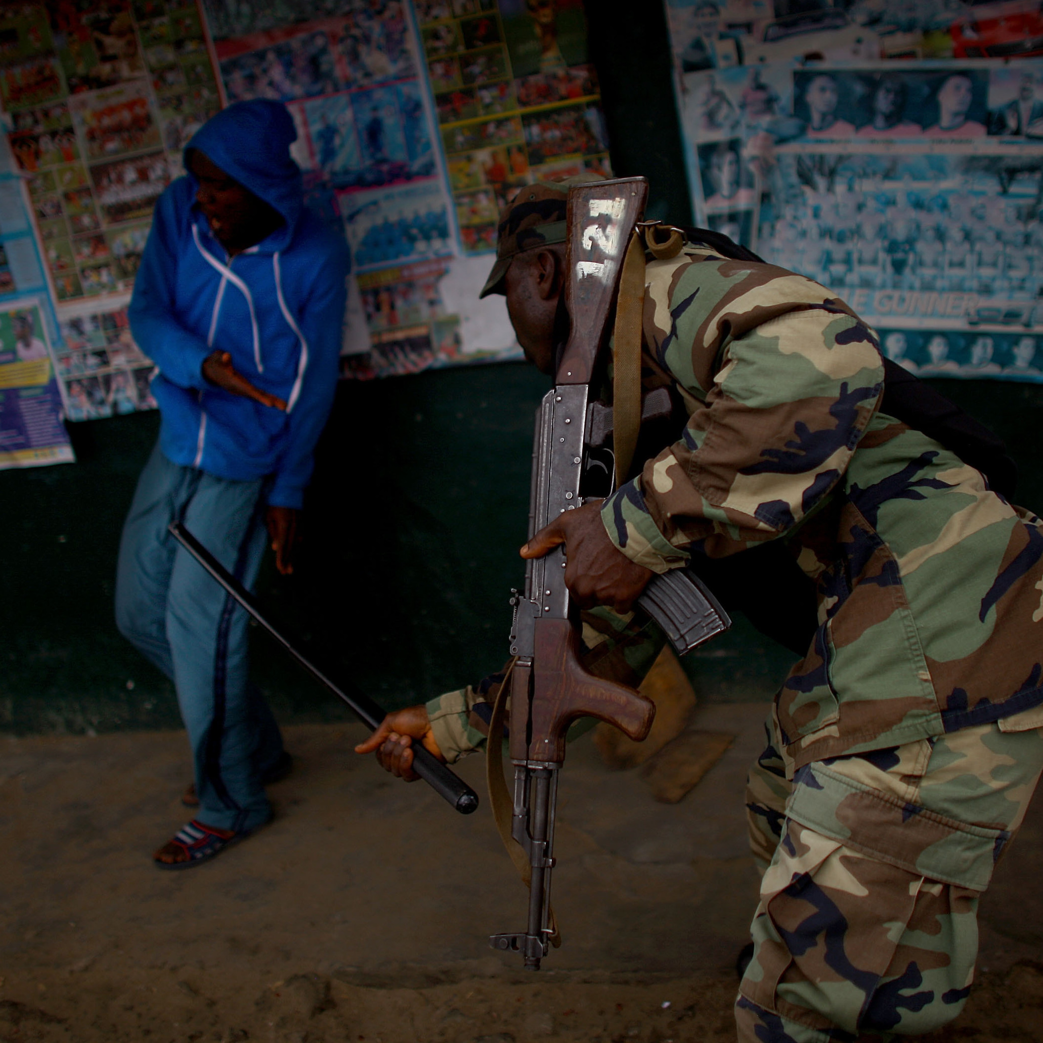 A member of Liberia's armed forces hits a West Point resident with a baton.