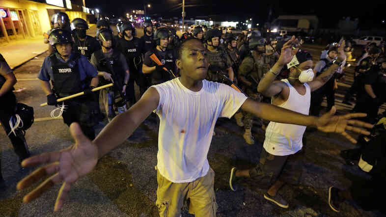 Protesters walk in front of a line of police as authorities try to disperse a demonstration in Ferguson, Mo., early Wednesday. The St. Louis suburb saw less violence than on recent nights of protests.