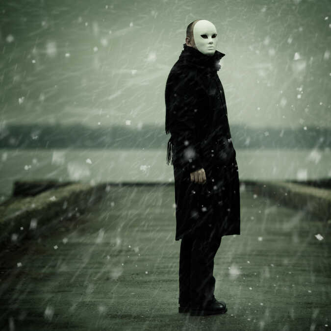 Man in a white mask standing in the snow beside a gray river.