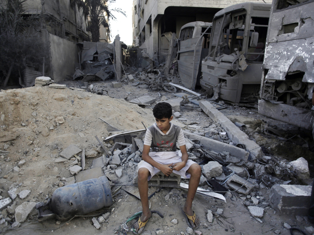 A Palestinian boy sits next to destroyed buses and houses on Wednesday, following overnight Israeli strikes in Gaza City.