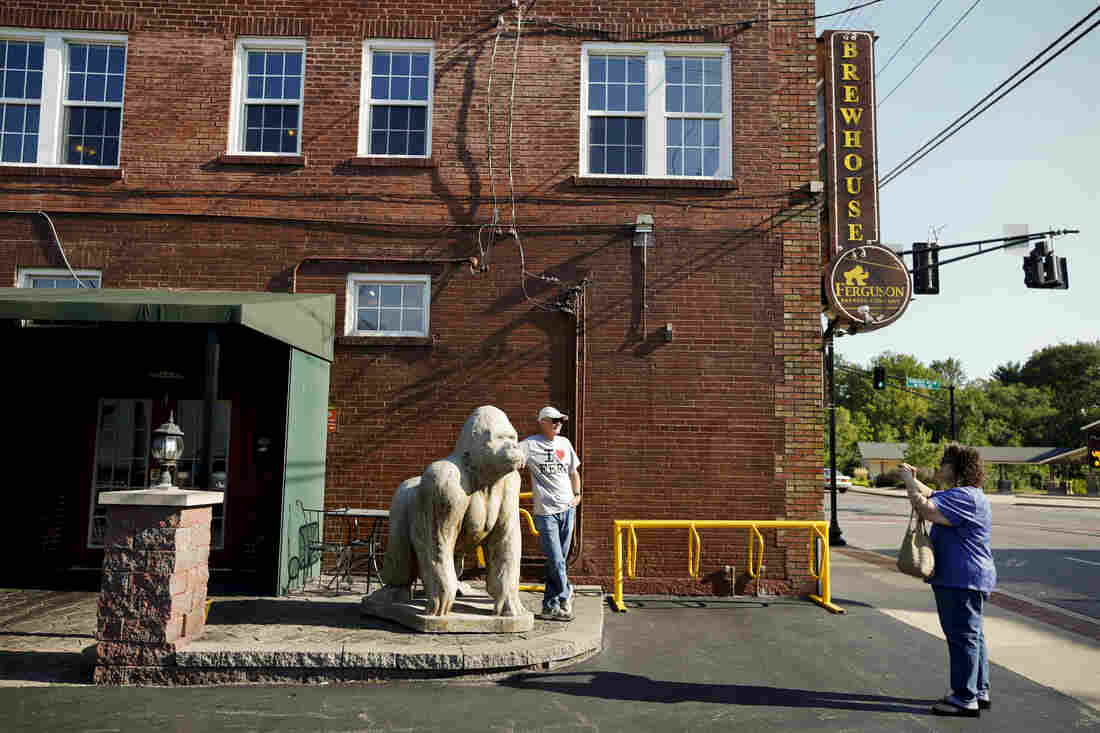 Linda Owen takes a photo of her husband, Al, in front of Ferguson Brewing Co. near the city's historic district. The couple are from an unincorporated section of St. Louis County and were visiting Ferguson. They don't get down to West Florissant much anymore, although Linda, a retired teacher, has former students who live there and said she worries about how they're doing.